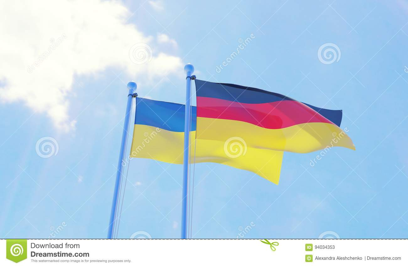 Ukraine and Germany, flags waving against blue sky