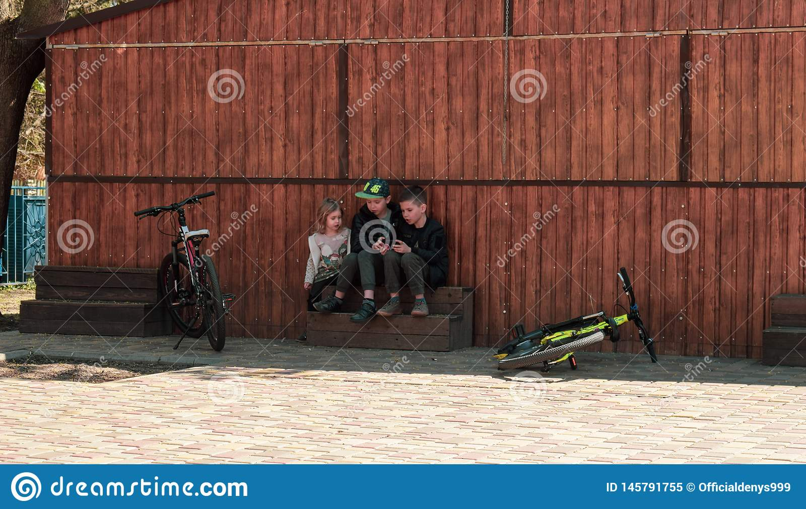 Ukraine, Kremenchug - April, 2019: Children are using a smartphones instead of riding bicycles