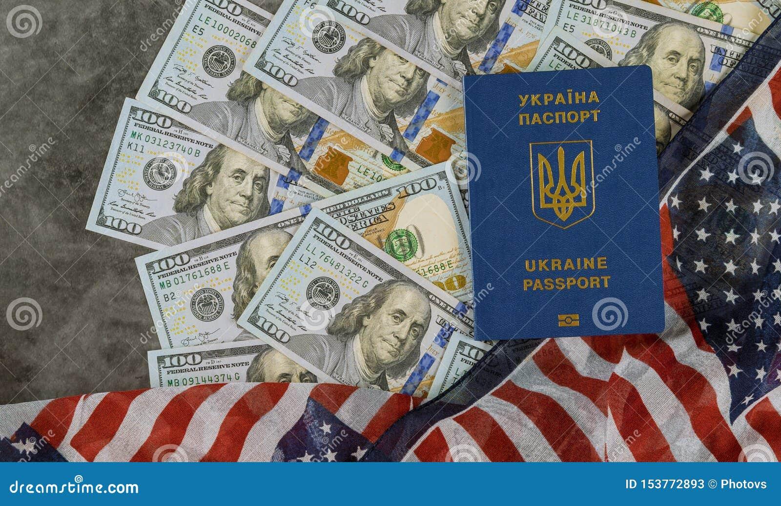 Ukrainian biometric passport in the US flag with bills of one hundred dollars