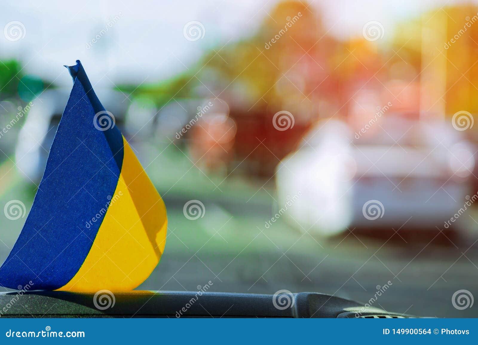 Ukrainsk flagga på exponeringsglas inom bilen