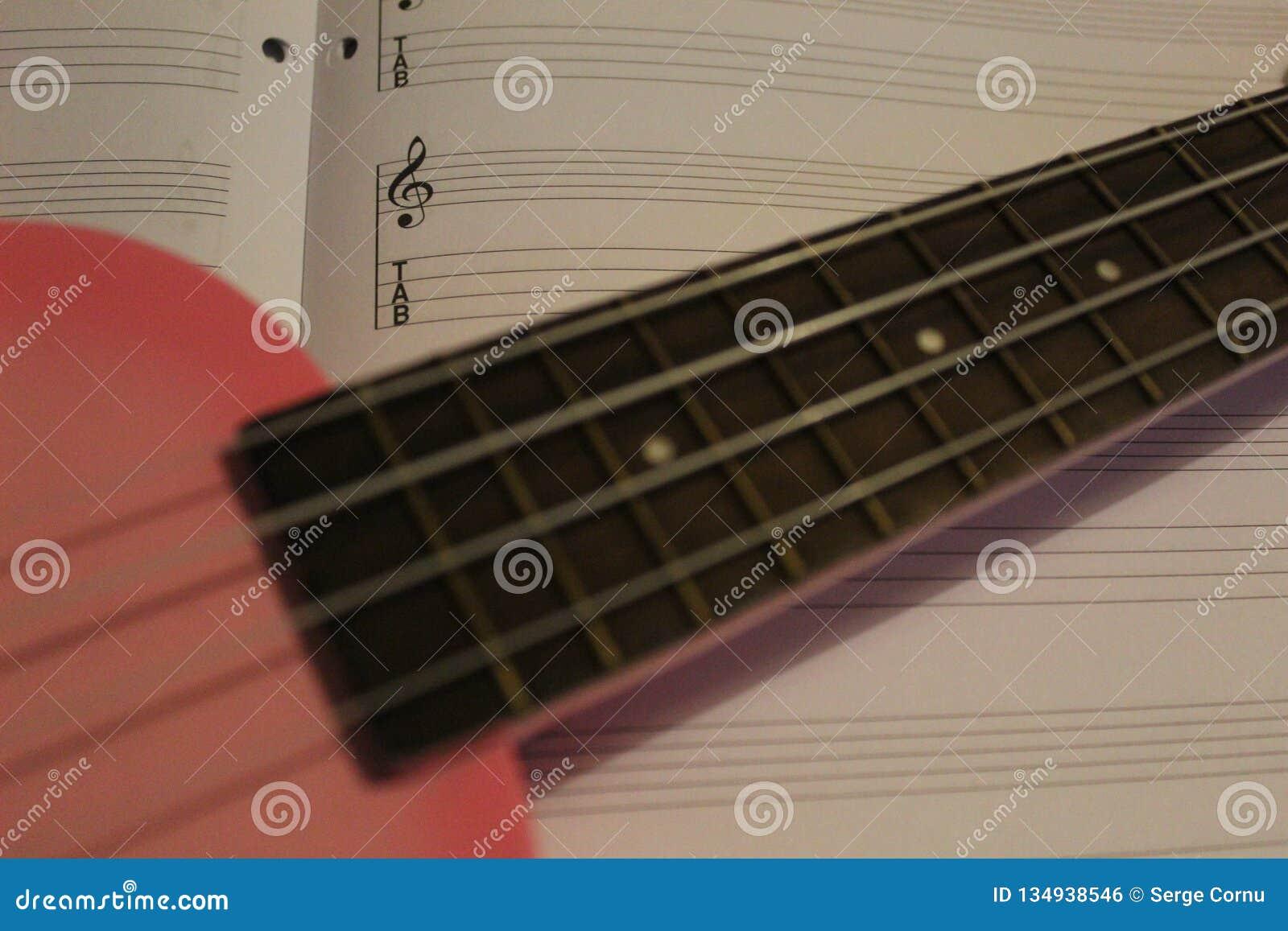 Ukulélé rose sur la musique de feuille