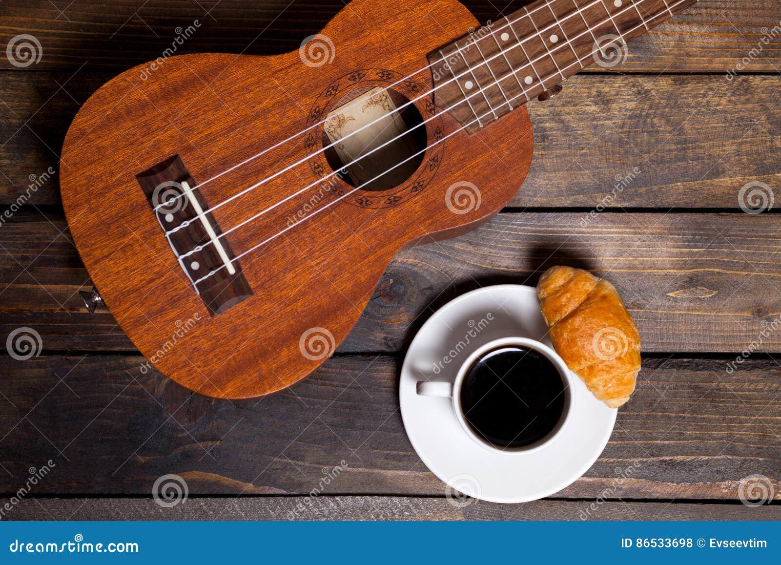Ukulele delle ukulele con la tazza di caffè ed il croissant