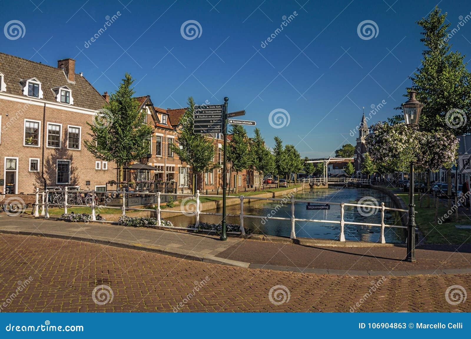 Ulica i most nad kanałem, cegła domami i kościelnym steeple przy zmierzchem w Weesp,