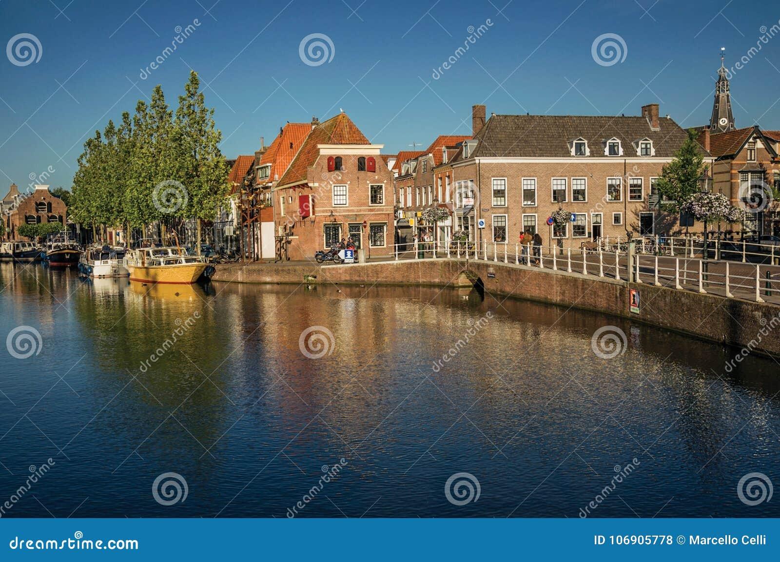 Ulica i most nad kanałem, cumować łodziami i cegła domami przy zmierzchem w Weesp,
