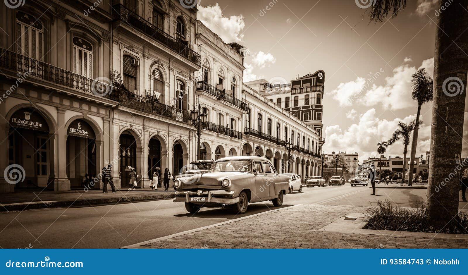 Uliczna sceneria na głównej ulicie z prowadnikowymi Amerykańskimi roczników samochodami w Hawańskim Kuba - Retro Seria Kuba SEPIO