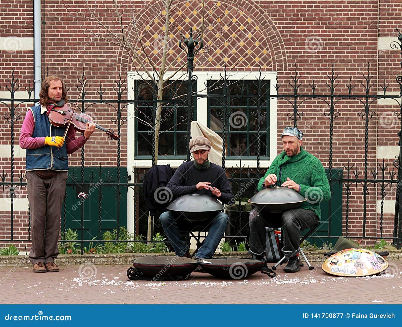 Uliczni muzycy z zrozumienie bębenami i skrzypcowy spełnianie w Amsterdam