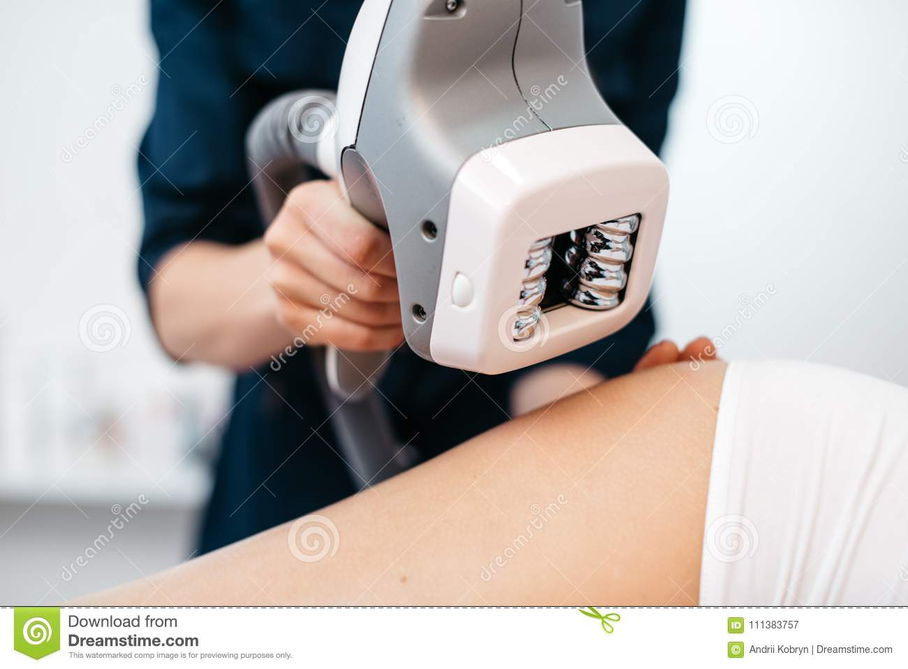 Ultrasound cavitation mashine in the hands of beautician. Close-up view. Woman is receiving the anti-cellulite treatment