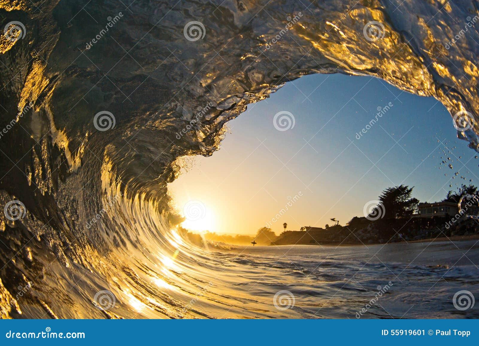 Um único tubo da onda de oceano no por do sol na praia