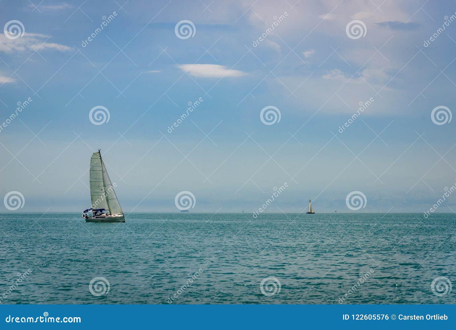 Um único veleiro é upwond indo no constance do lago