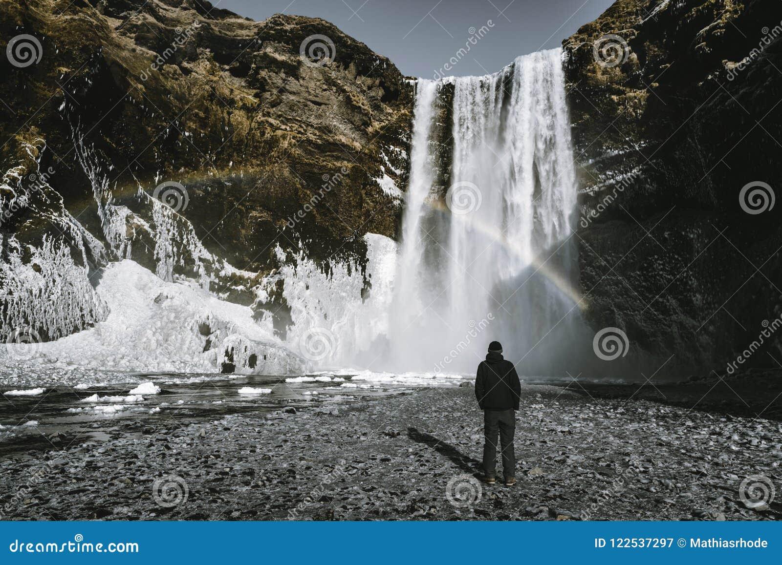 Um admirnig que da pessoa a beleza da cachoeira de Skogafoss com arco-íris encontrou em Islândia