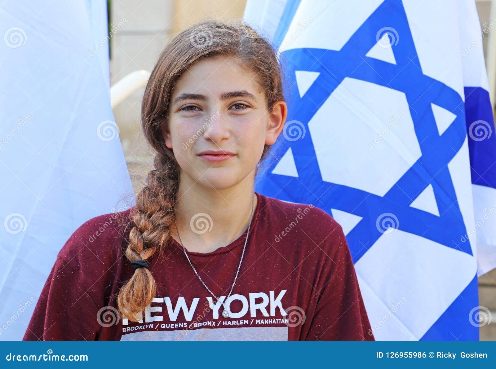 Um adolescente ao lado de uma bandeira israelita