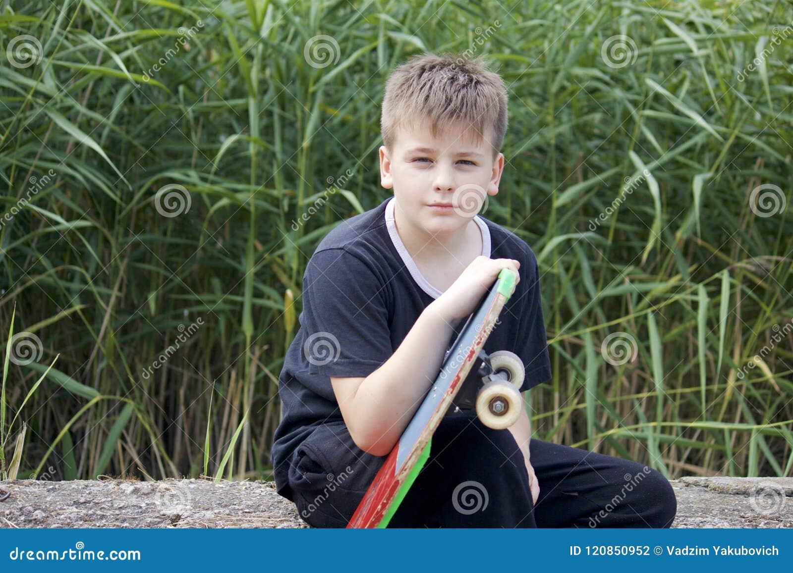Um adolescente com um skate Guarda um patim nas mãos