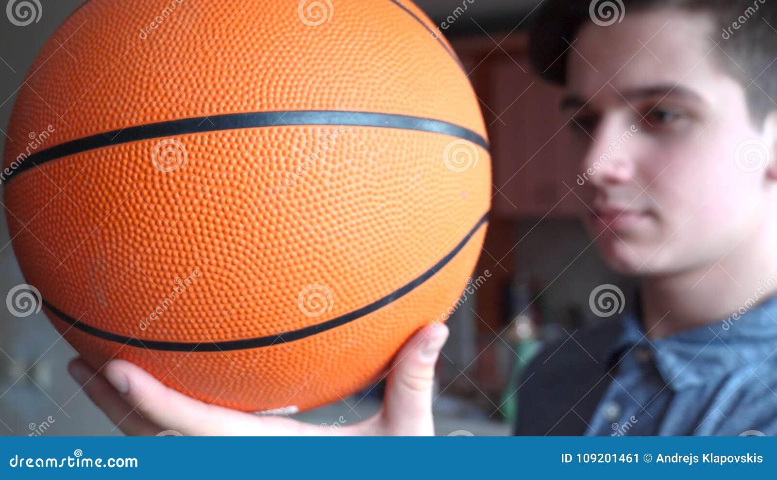 Um adolescente considerável do menino está guardando um basketballl