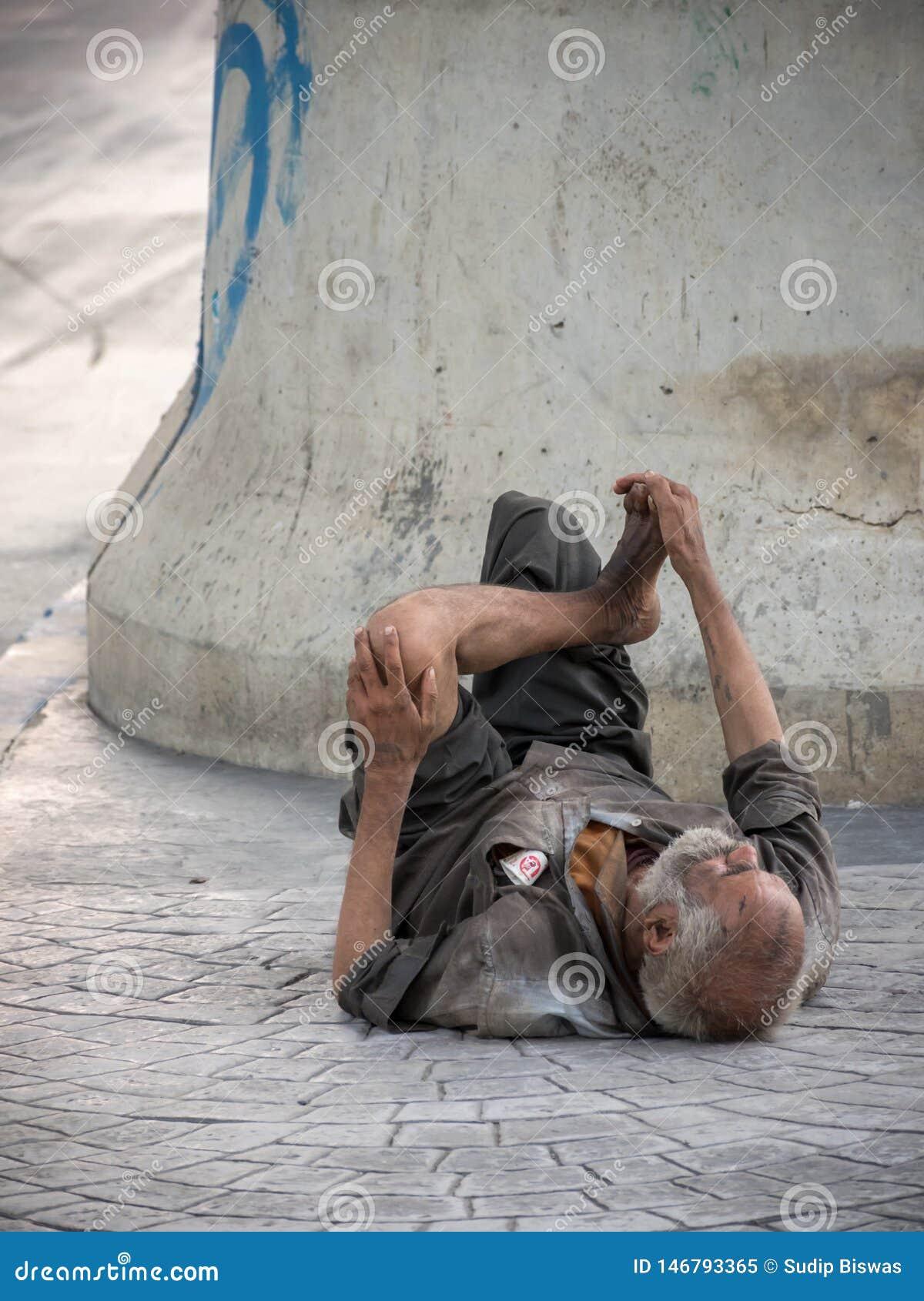 Um ancião é desabrigado ou mendigo que dorme ao lado da rua