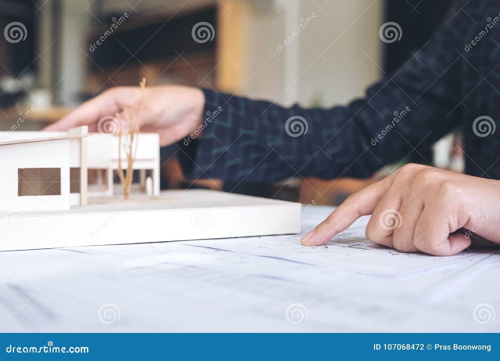 Um arquiteto que trabalha e que aponta no modelo da arquitetura com papel de desenho da loja