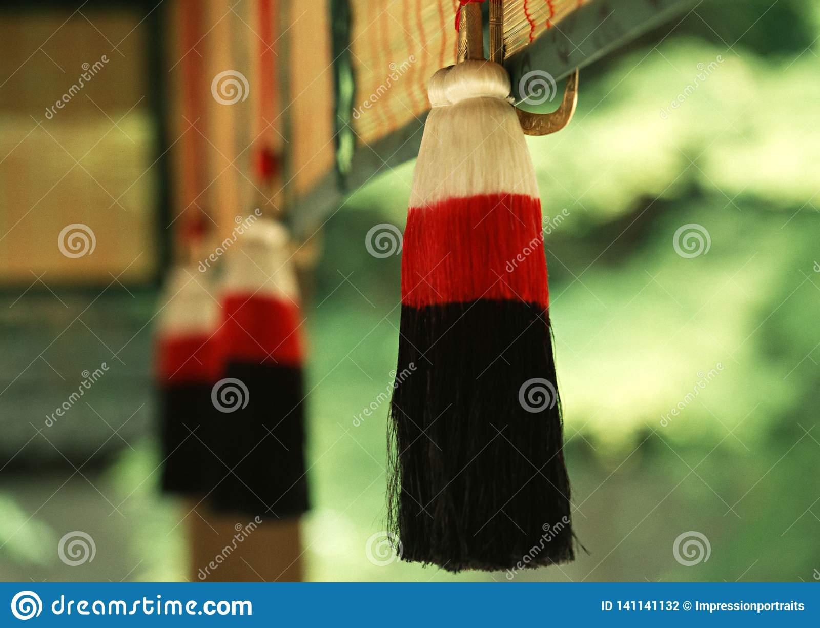 Um artigo decorativo tradicional de suspensão vermelho e preto japonês com o fundo verde borrado
