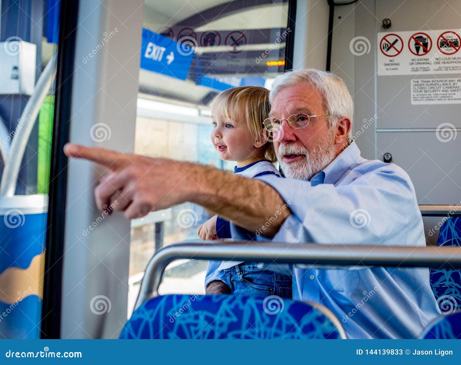 Um avô passa o tempo da qualidade com seu neto em um trem do trilho