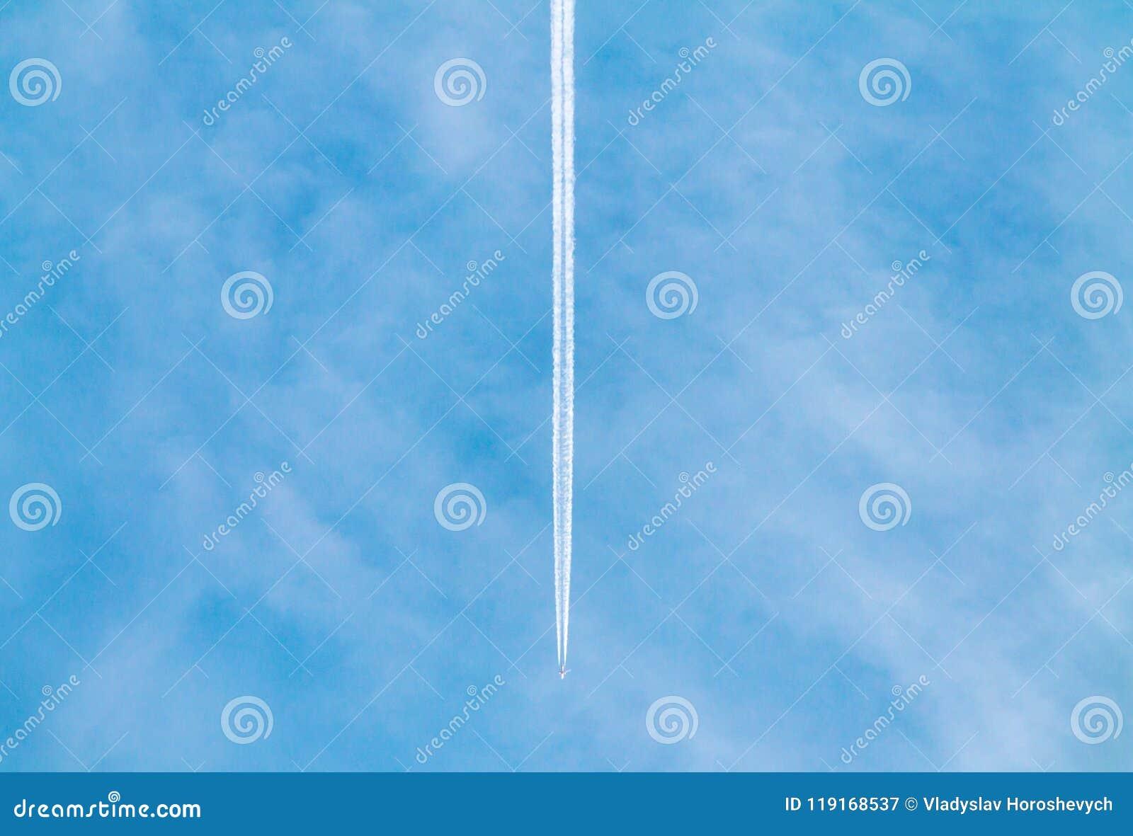 Um avião com o contrail alto no céu, dois aviões da turbina que voam altamente no céu azul