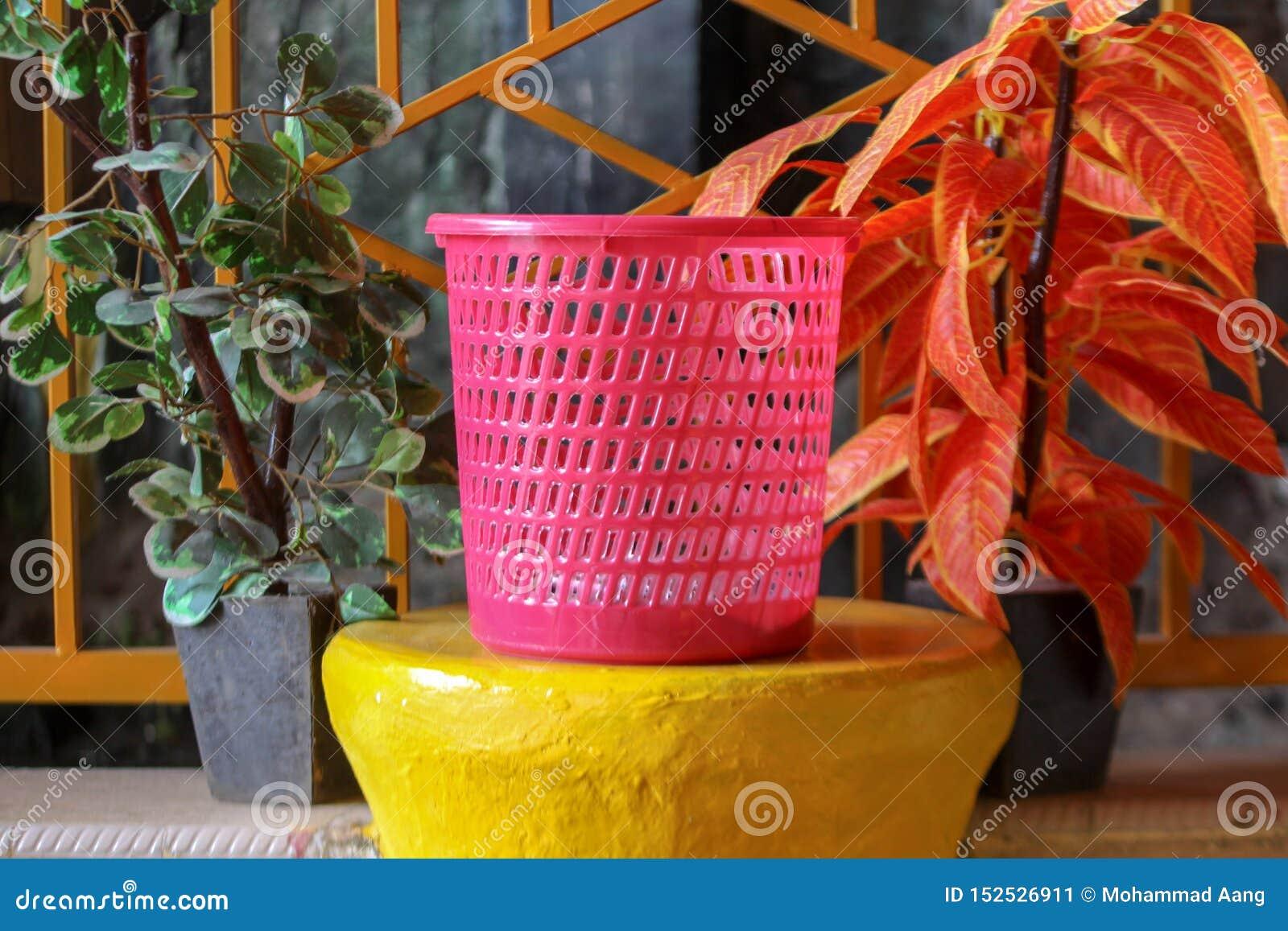 Um balde do lixo cor-de-rosa com um fundo floral no jardim