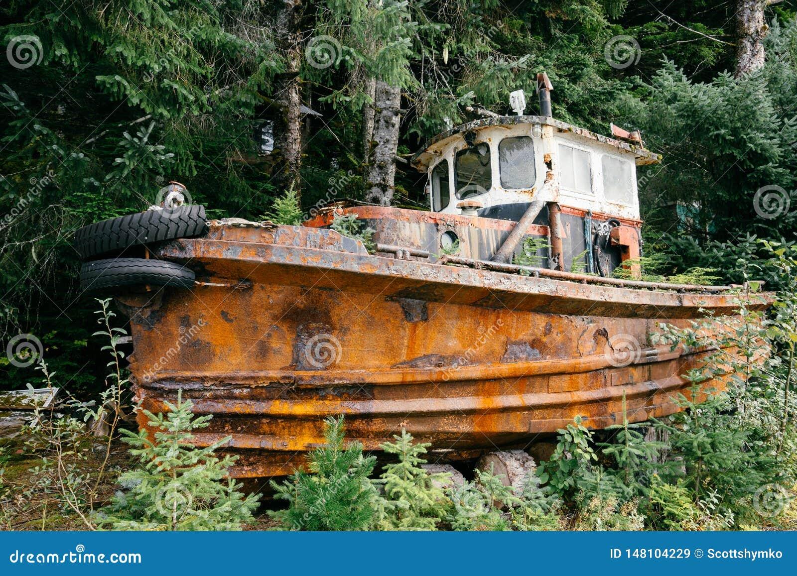 Um barco de pesca abandonado oxidado por árvores