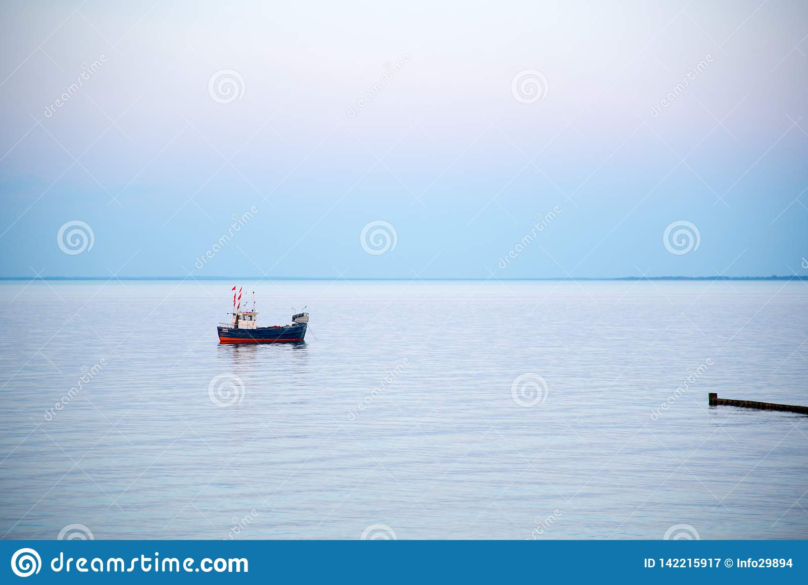 Um barco de pesca pequeno no mar no amanhecer