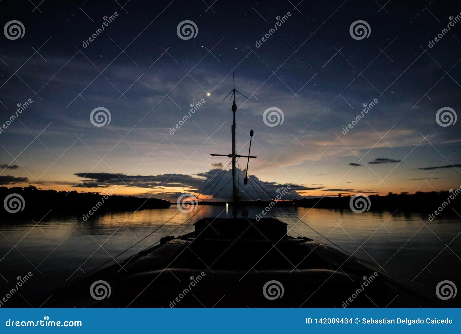 Um barco navega o rio de Javari após o por do sol