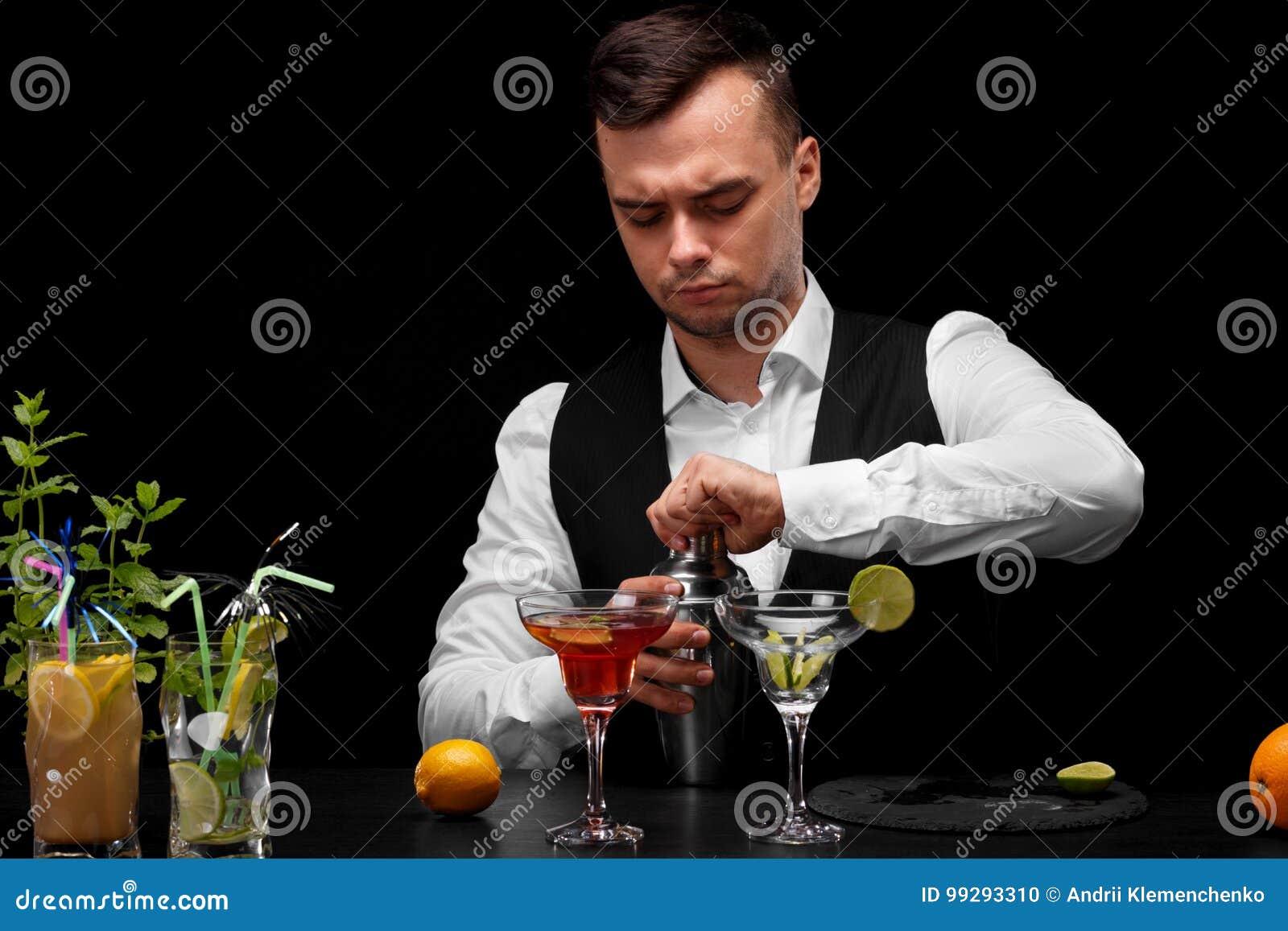 Um barman abre um abanador, um contador com vidros do margarita, limão da barra, cal, cocktail em um fundo preto