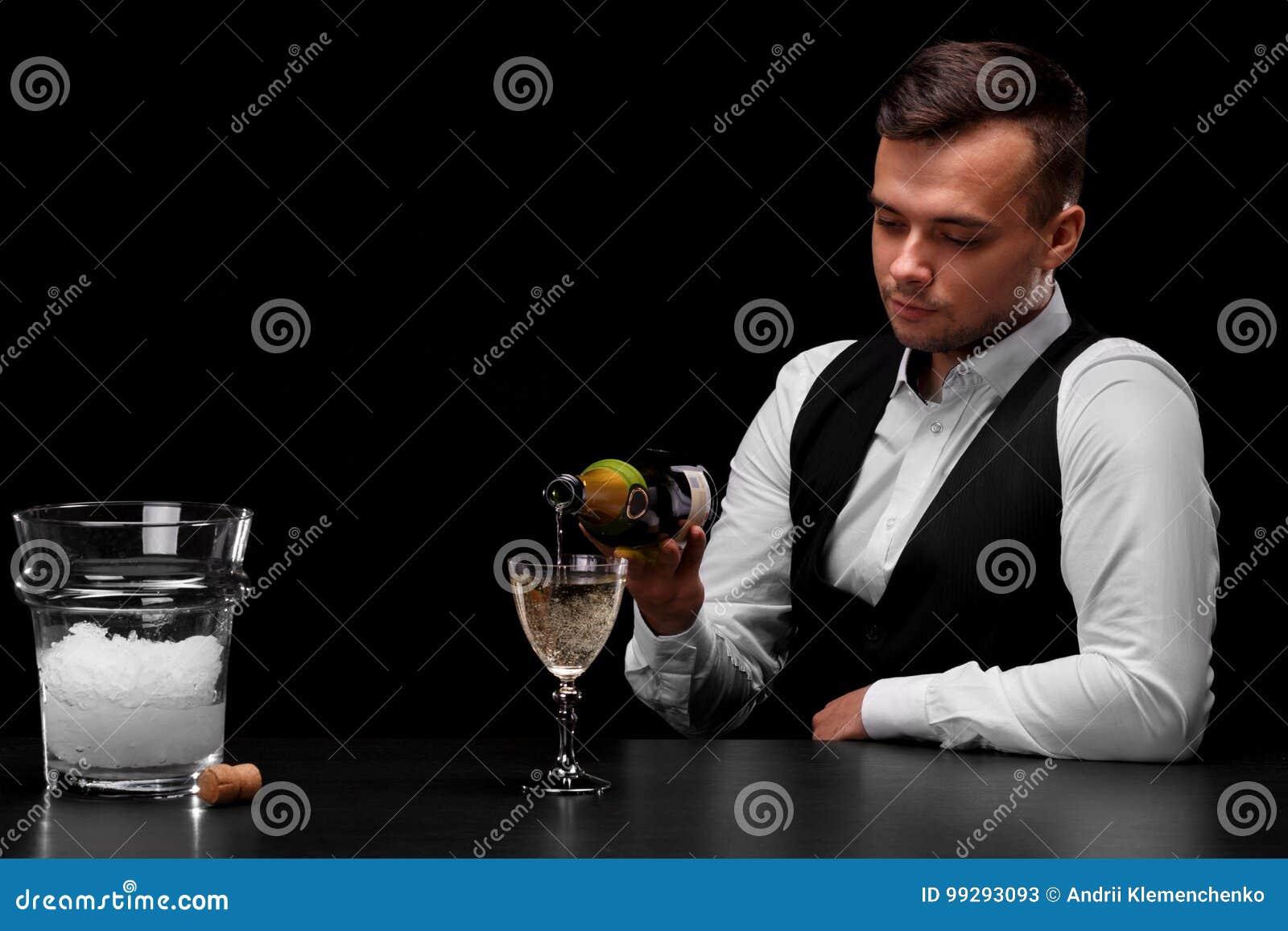 Um barman atrativo derrama o champanhe em um vidro, uma cubeta com gelo, uma cortiça em um fundo preto