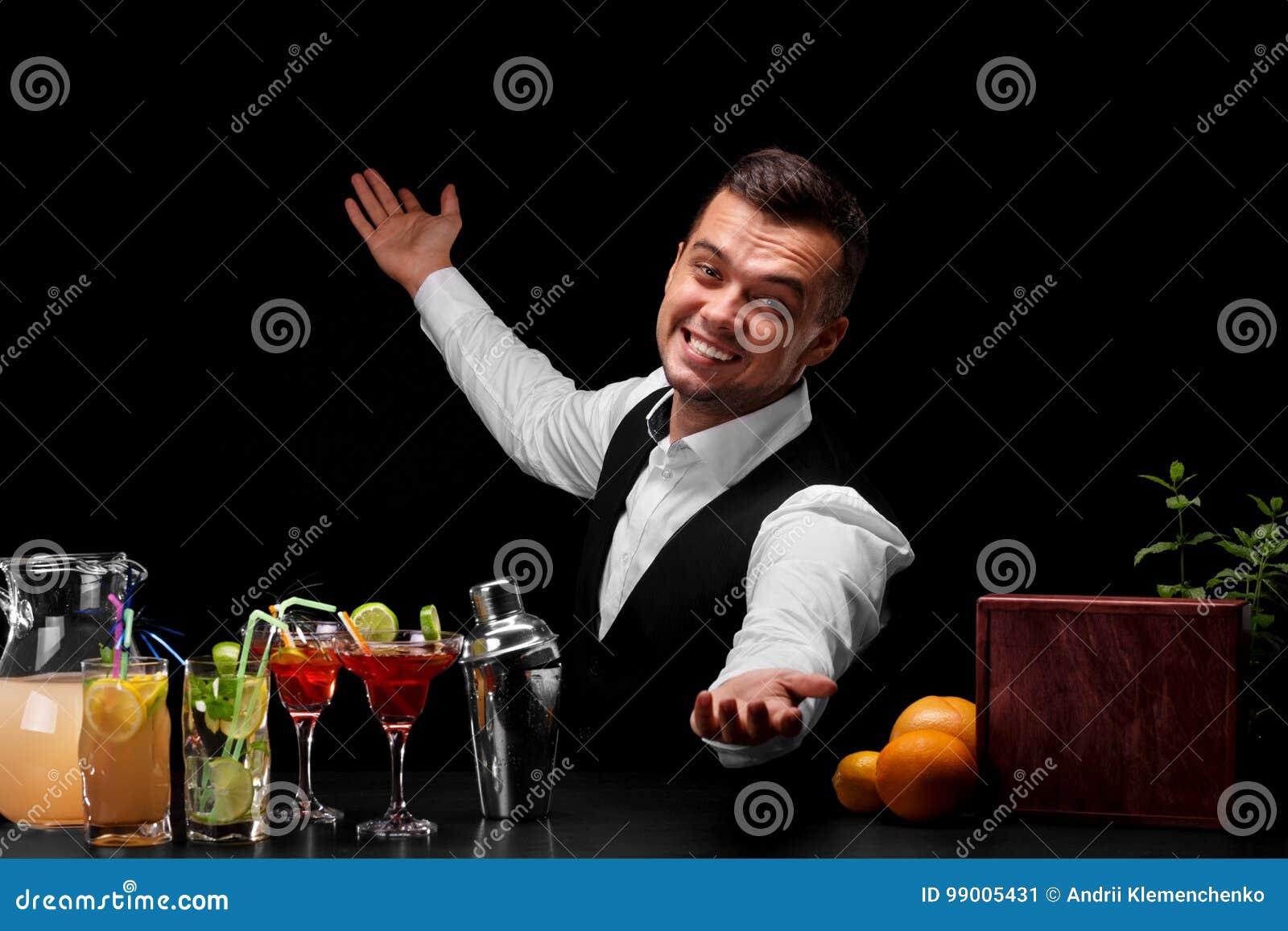 Um barman feliz em um terno clássico em um fundo preto Muitos ingredientes coloridos para cocktail em uma tabela