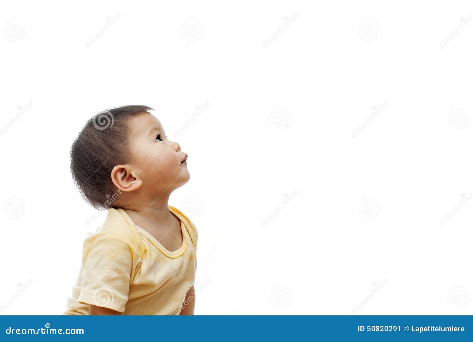 Um bebê olha acima com a roupa amarela, não olhando a câmera, isolada no branco