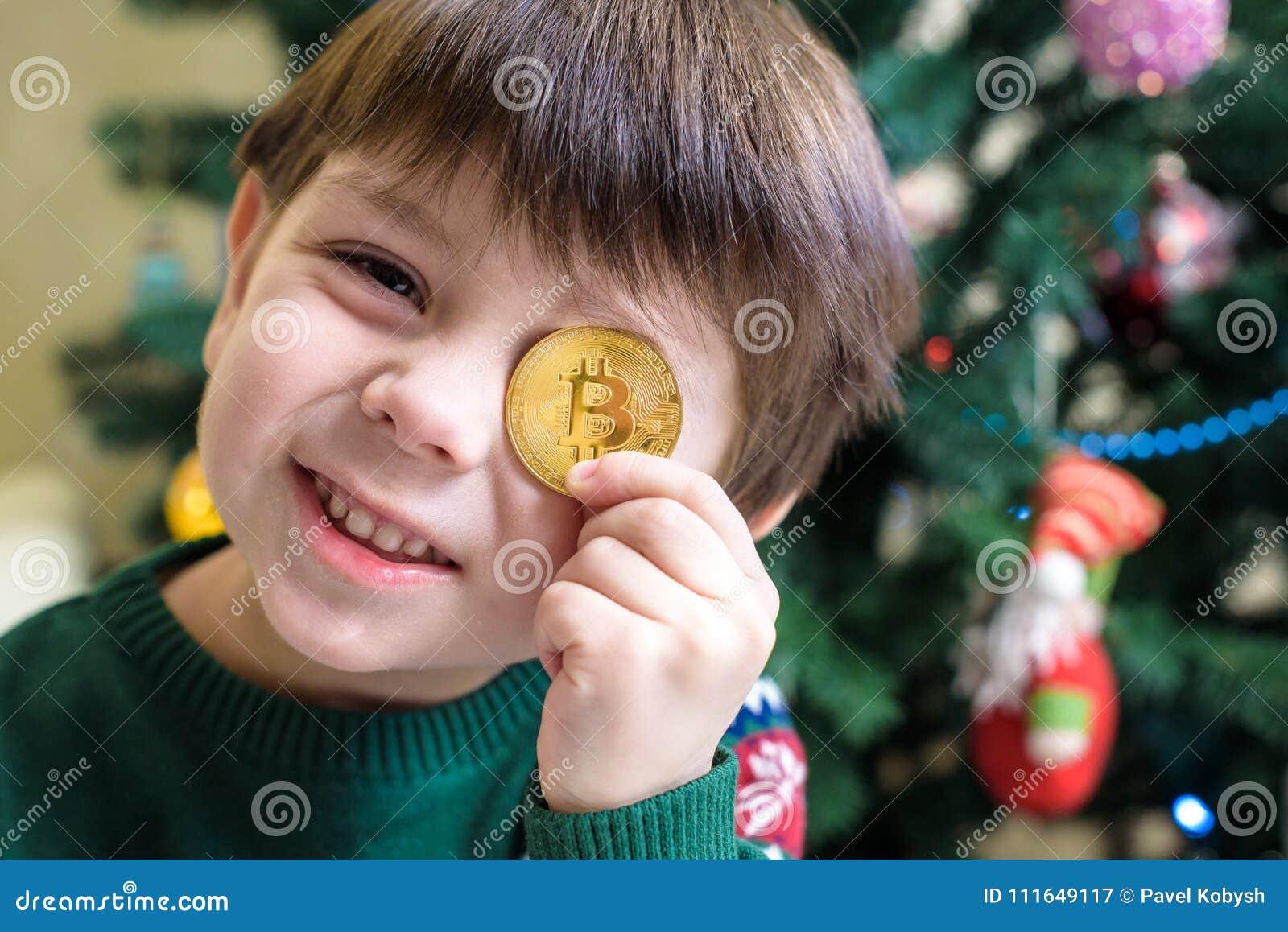 Um Bitcoin na mão do menino novo Conceito Ouro digital cripto