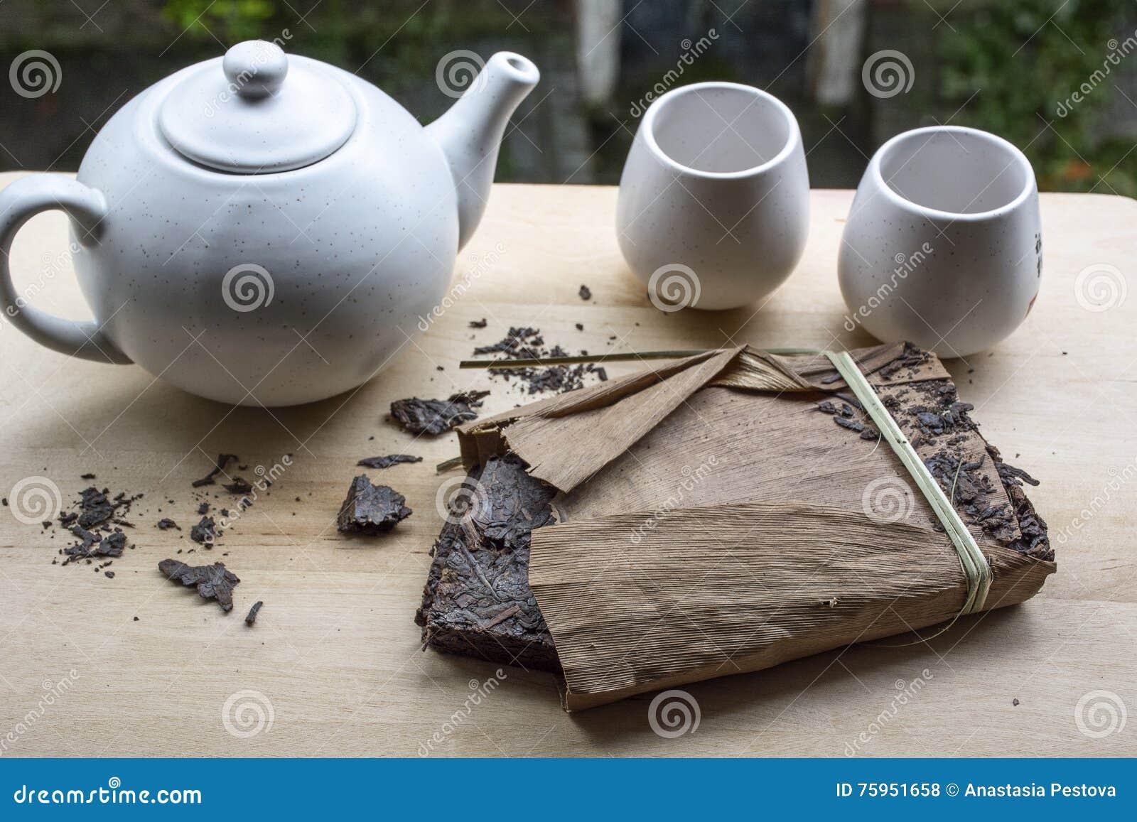 Um bloco do chá chinês preto com teakettle branco e dois copos