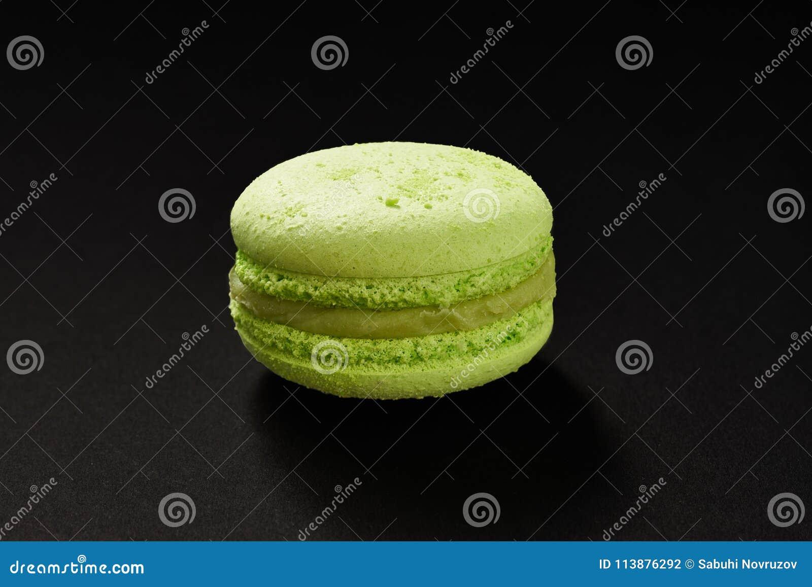 Um bolo da cor verde do macarrão Bolinho de amêndoa delicioso do pistache isolado no fundo preto Cookie doce francesa