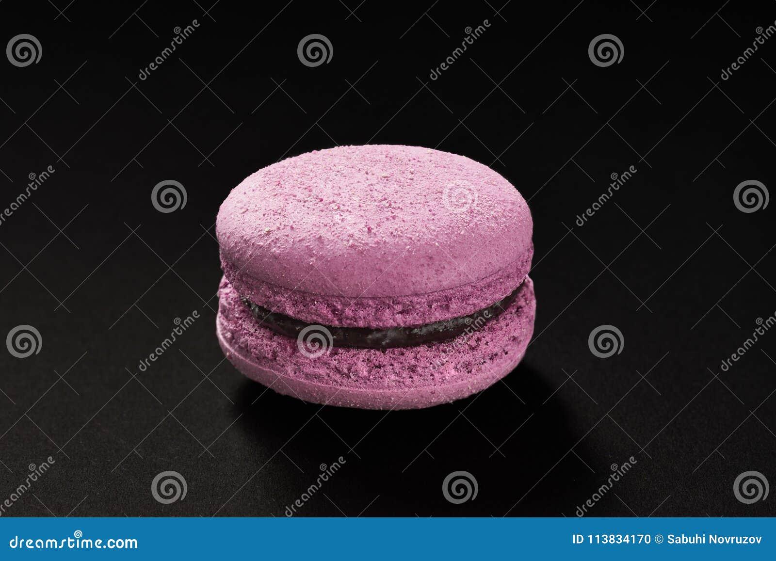 Um bolo da cor da violeta do macarrão Bolinho de amêndoa delicioso do corinto isolado no fundo preto Cookie doce francesa