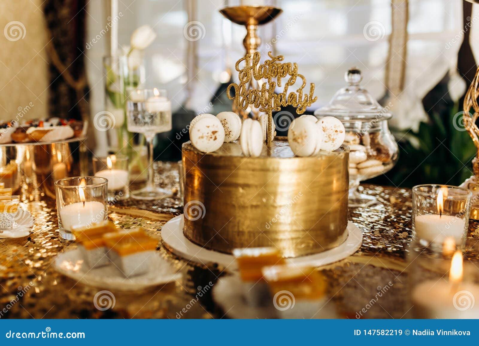 Um bolo de aniversário dourado é decorado com macarrão