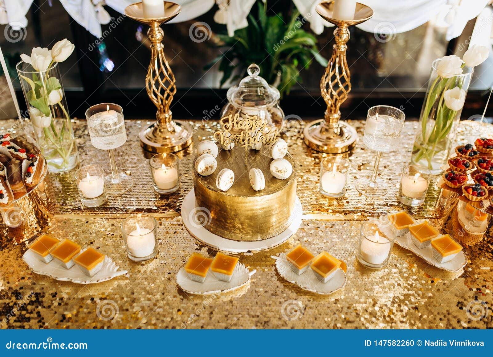 Um bolo de anivers?rio dourado ? decorado com macarr?o