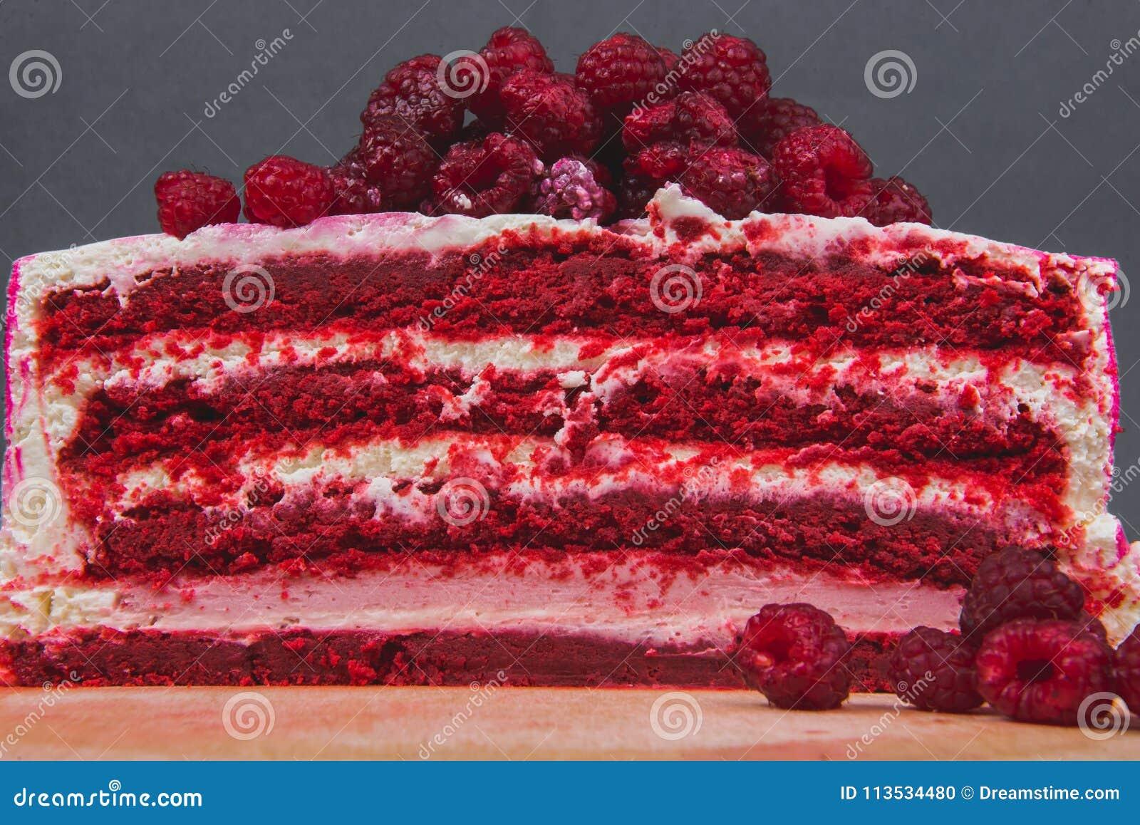 Um bolo delicioso decorado com framboesas em um fundo cinzento