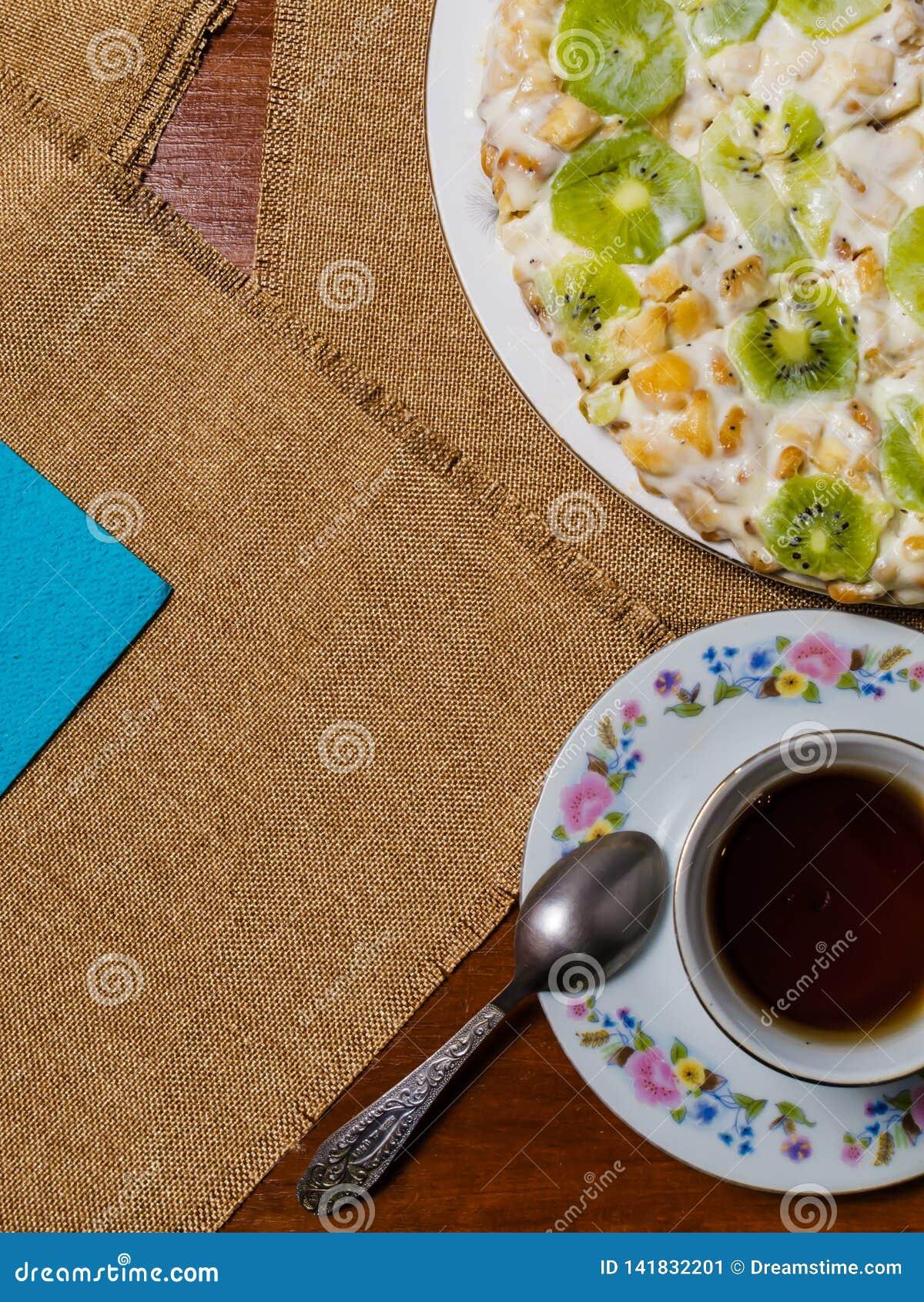 Um bolo feito dos biscoitos, decorados com fatias do quivi, mentiras em uma placa branca ao lado de uns pires e um copo do chá pr