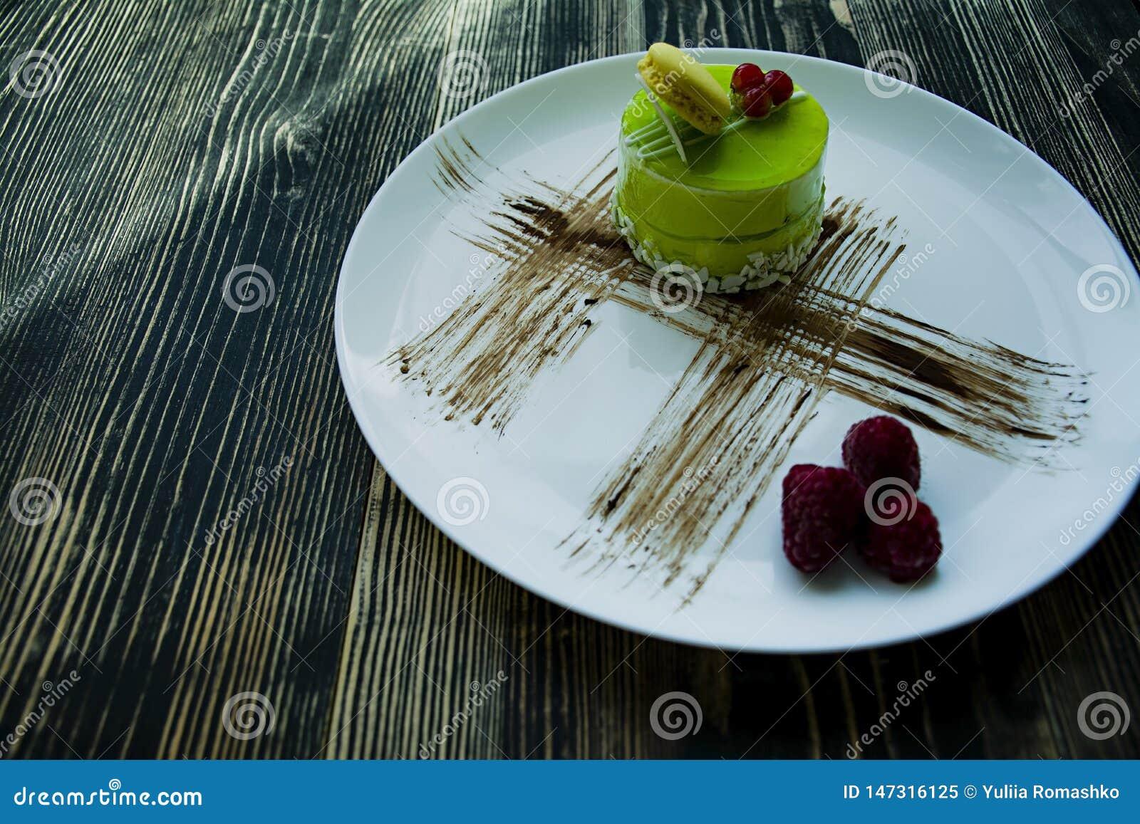 Um bolo pequeno do pistache com um revestimento verde e decorado com viburnum, molho dos confeitos em um fundo preto Vista latera