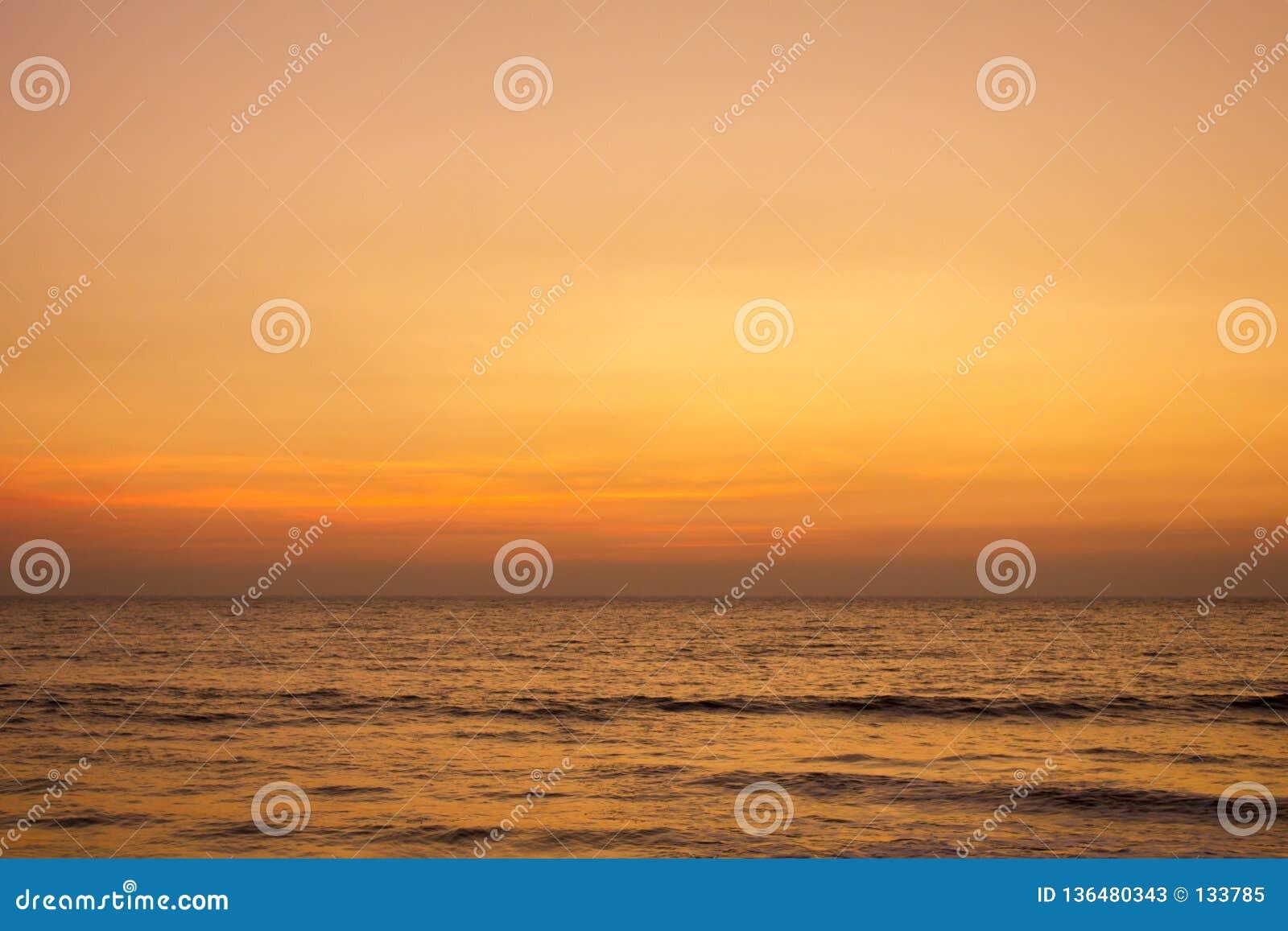 Um céu cor-de-rosa cinzento amarelo brilhante do por do sol sobre o oceano
