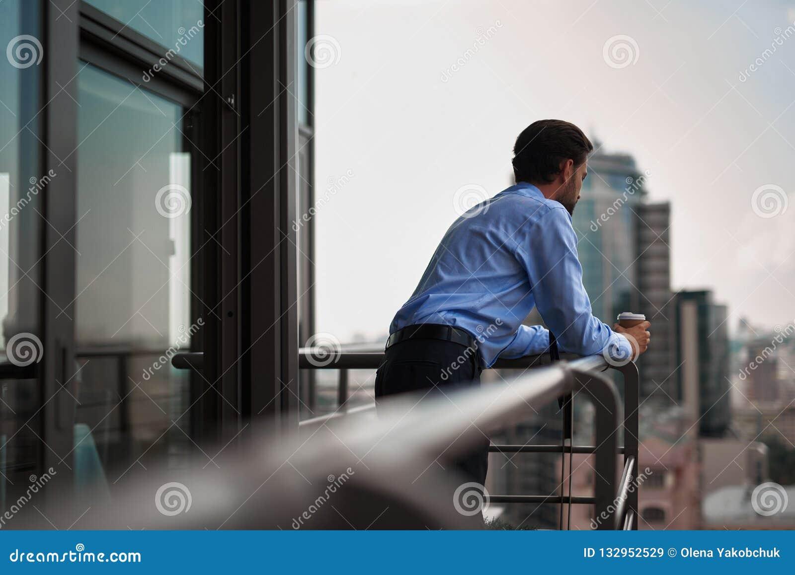 Um café bebendo do trabalhador masculino no balcão do escritório