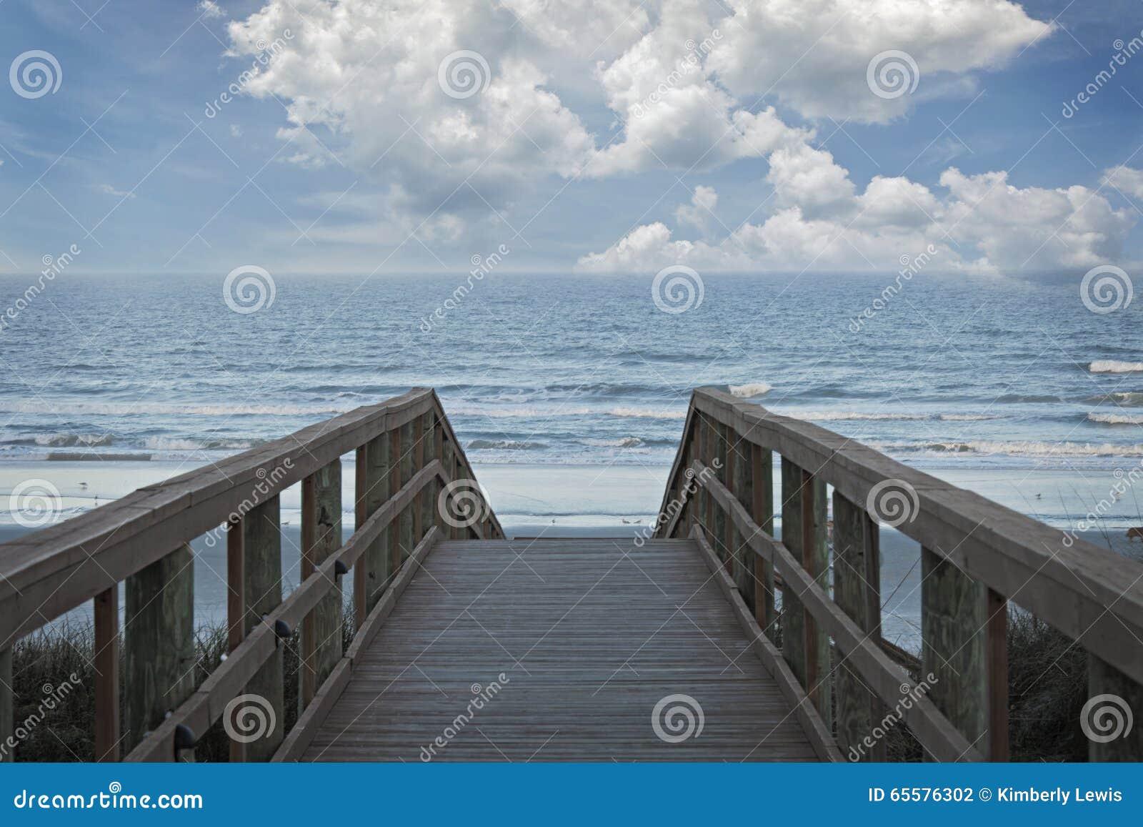 Um cais de madeira que conduz ao oceano com as nuvens macias brancas