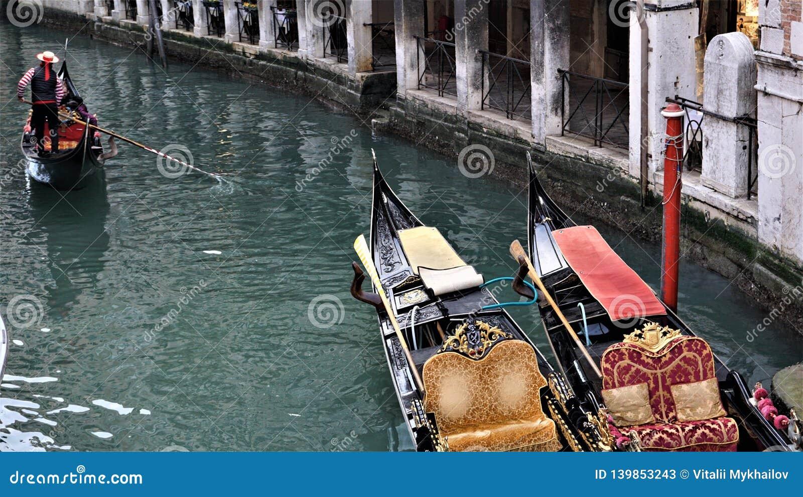 Um canal com duas gôndola e um gondoleiro que flutua perto deles em Veneza, Itália