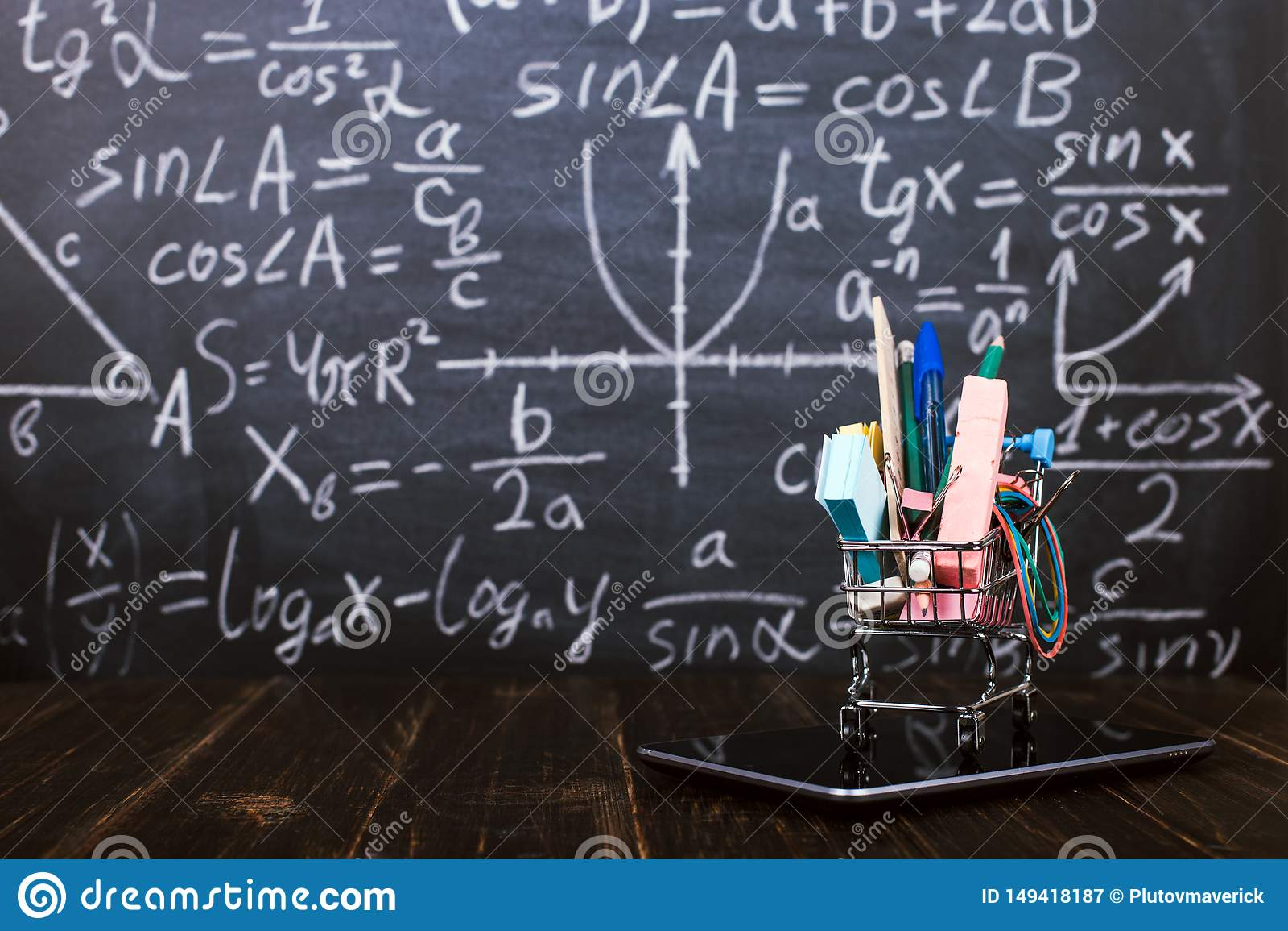 Um carrinho de compras com fontes de escola na tabuleta, na tabela contra o quadro do fundo Conceito de volta ? prepara??o da esc