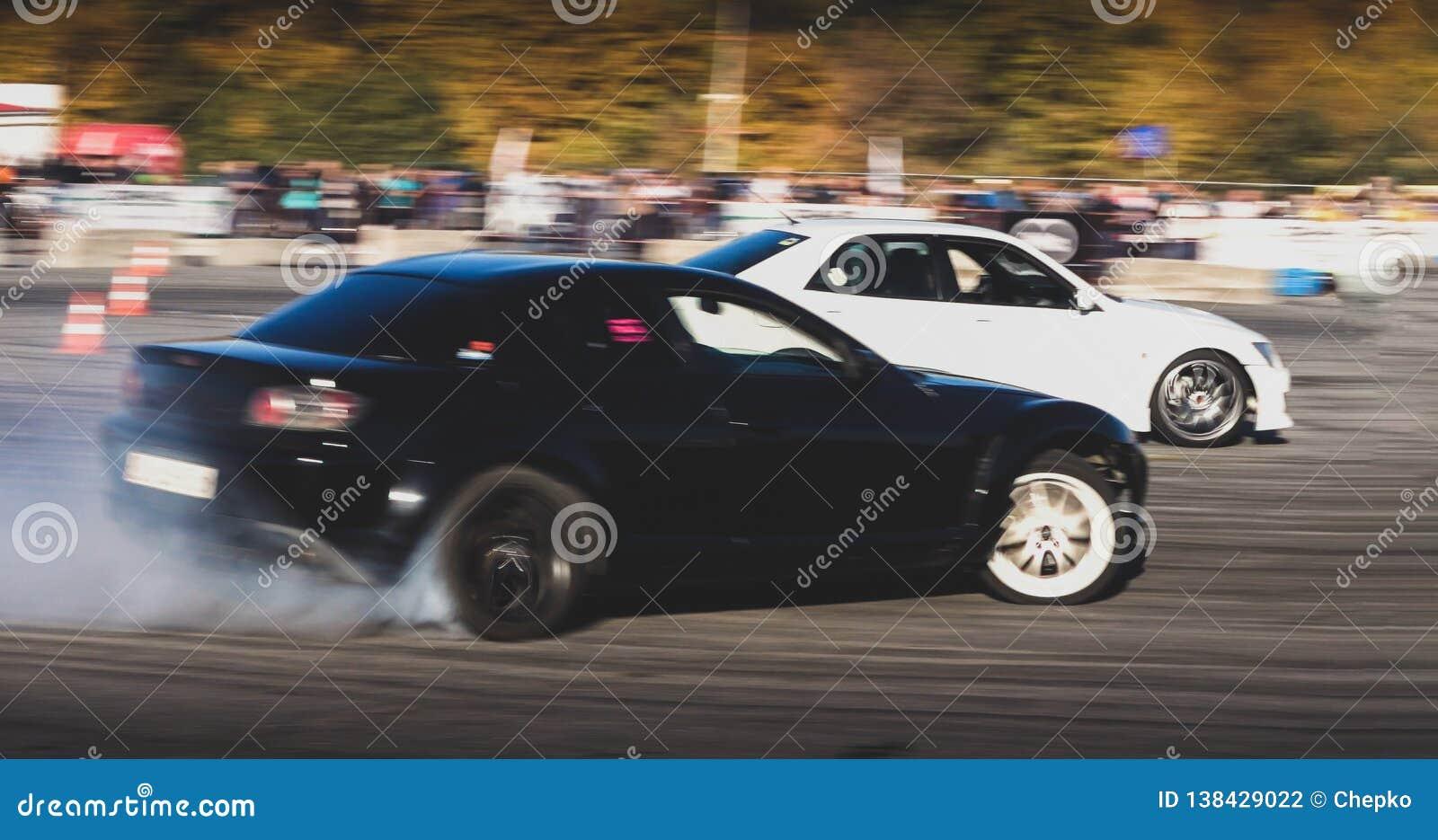 Um carro de competência da tração na ação com os pneus de fumo na mostra