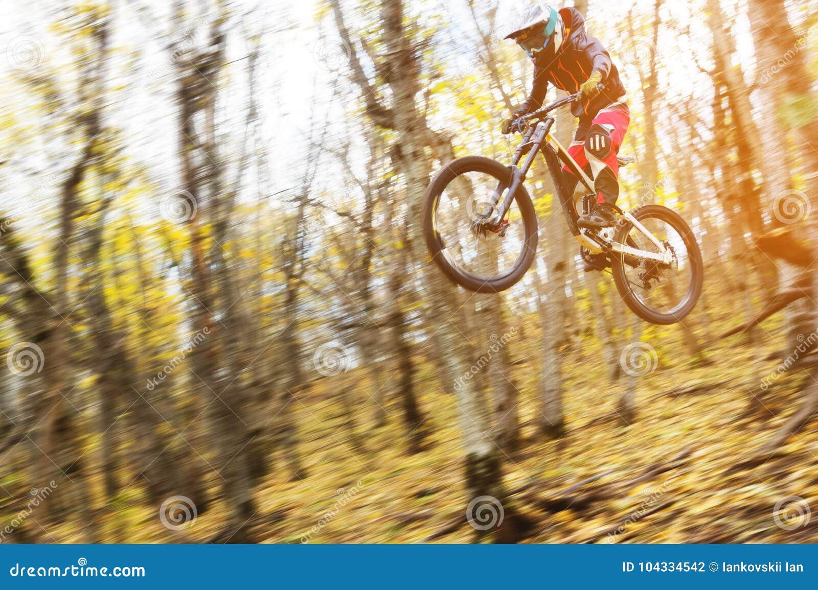 Um cavaleiro novo na roda de seu Mountain bike faz um truque no salto no trampolim da montanha em declive