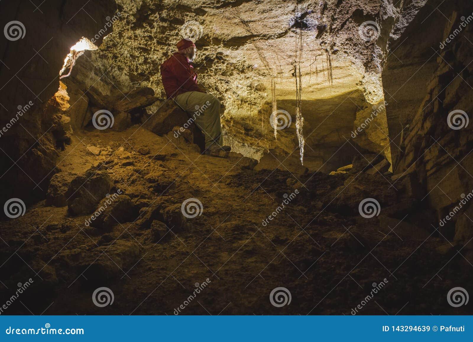 Um caver explora uma caverna com uma lanterna Odessa Catacombs, Ucrânia