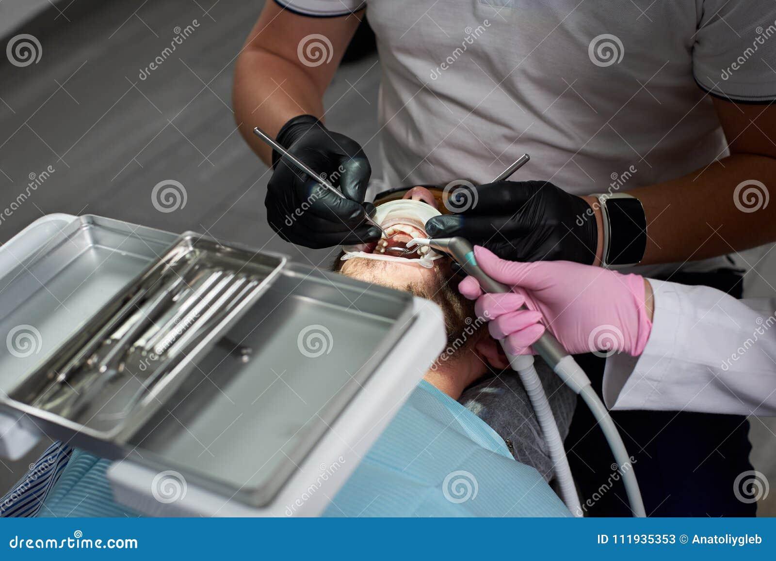 Um cliente de uma odontologia moderna está tendo seus dentes atendidos por um dentista em luvas de borracha pretas