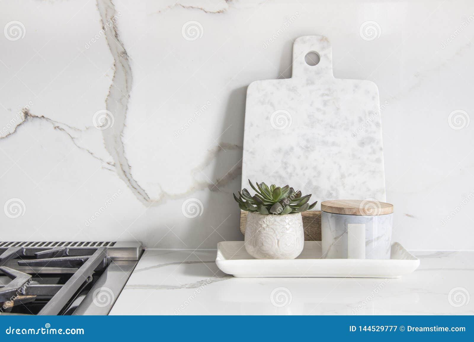 Um close up bonito de uma cozinha projetada, com a bancada e backsplash de vista de mármore de quartzo