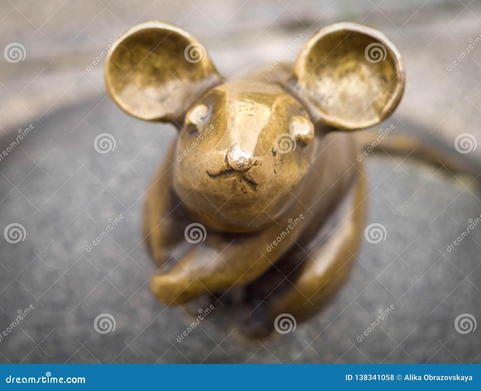 Um close-up da escultura do rato com os grandes escultores S das orelhas Plotnikov e S Yurkus que executa desejos no cobbled